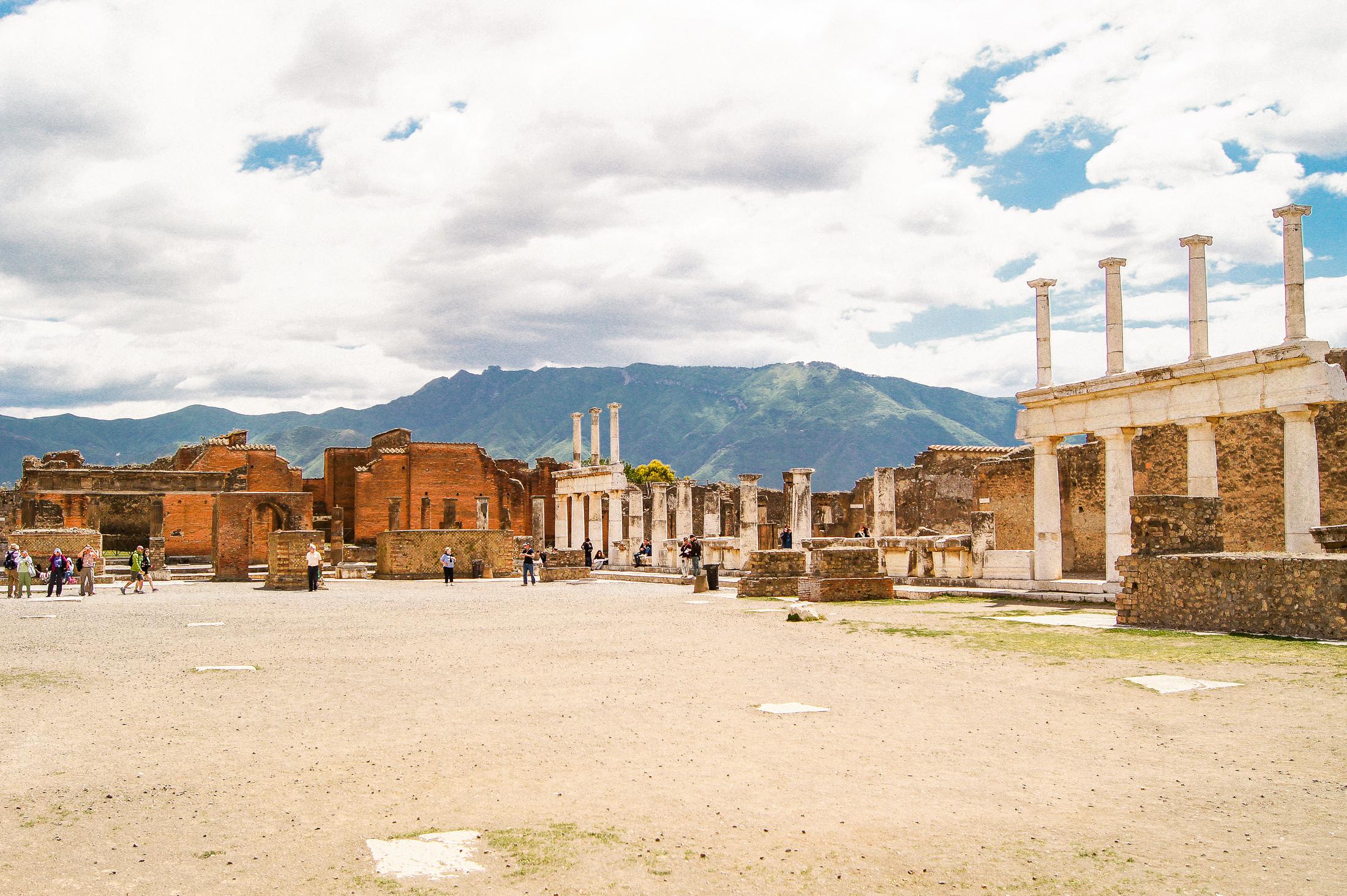 Ett torg i staden Pompeji med ruiner och pelare, berg i bakgrunden.