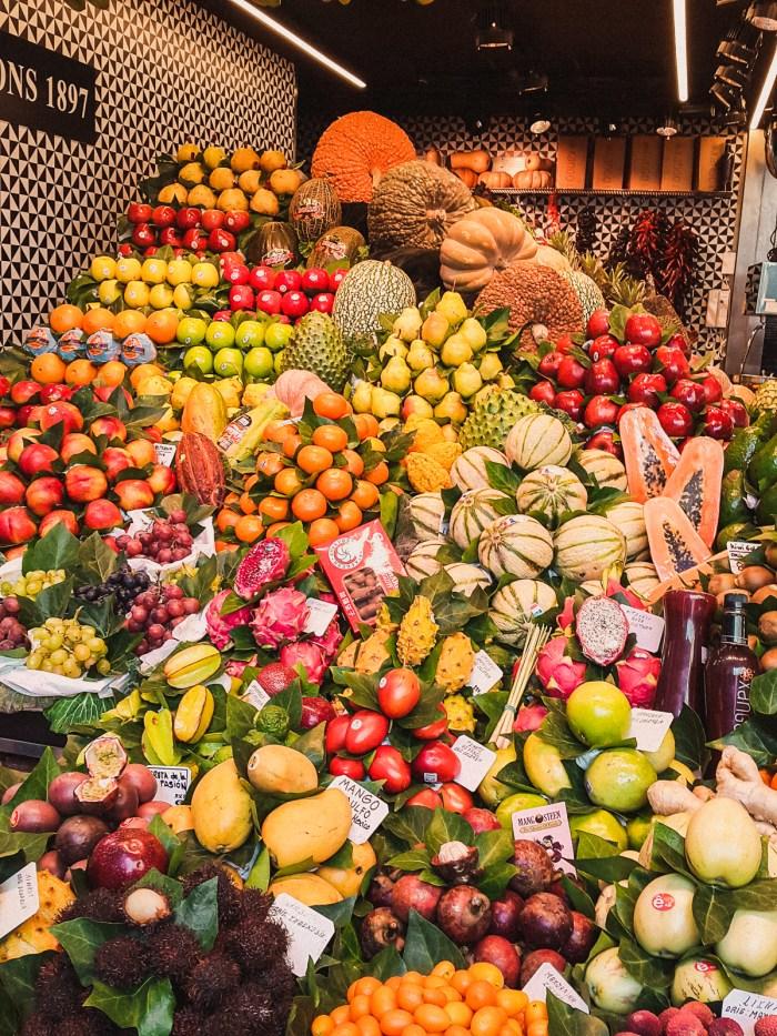 massor av olika frukter i en stor hög på marknaden.