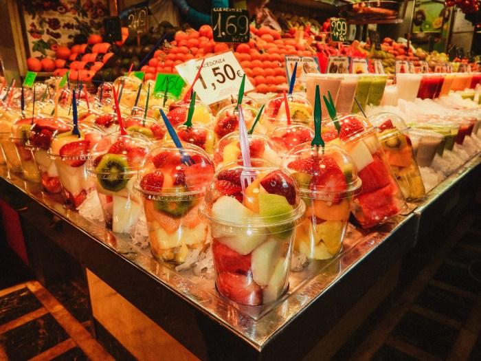 fruktbitar i plastmuggar på ett bord.