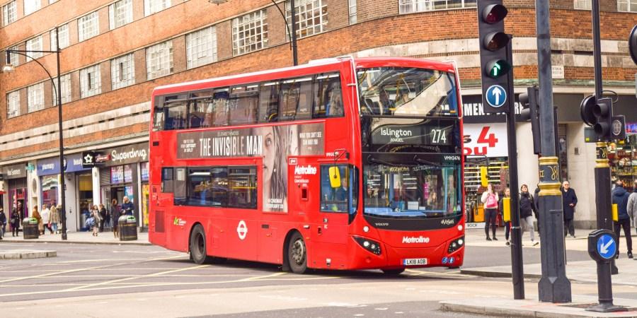 en röd london-buss kör på gatan.