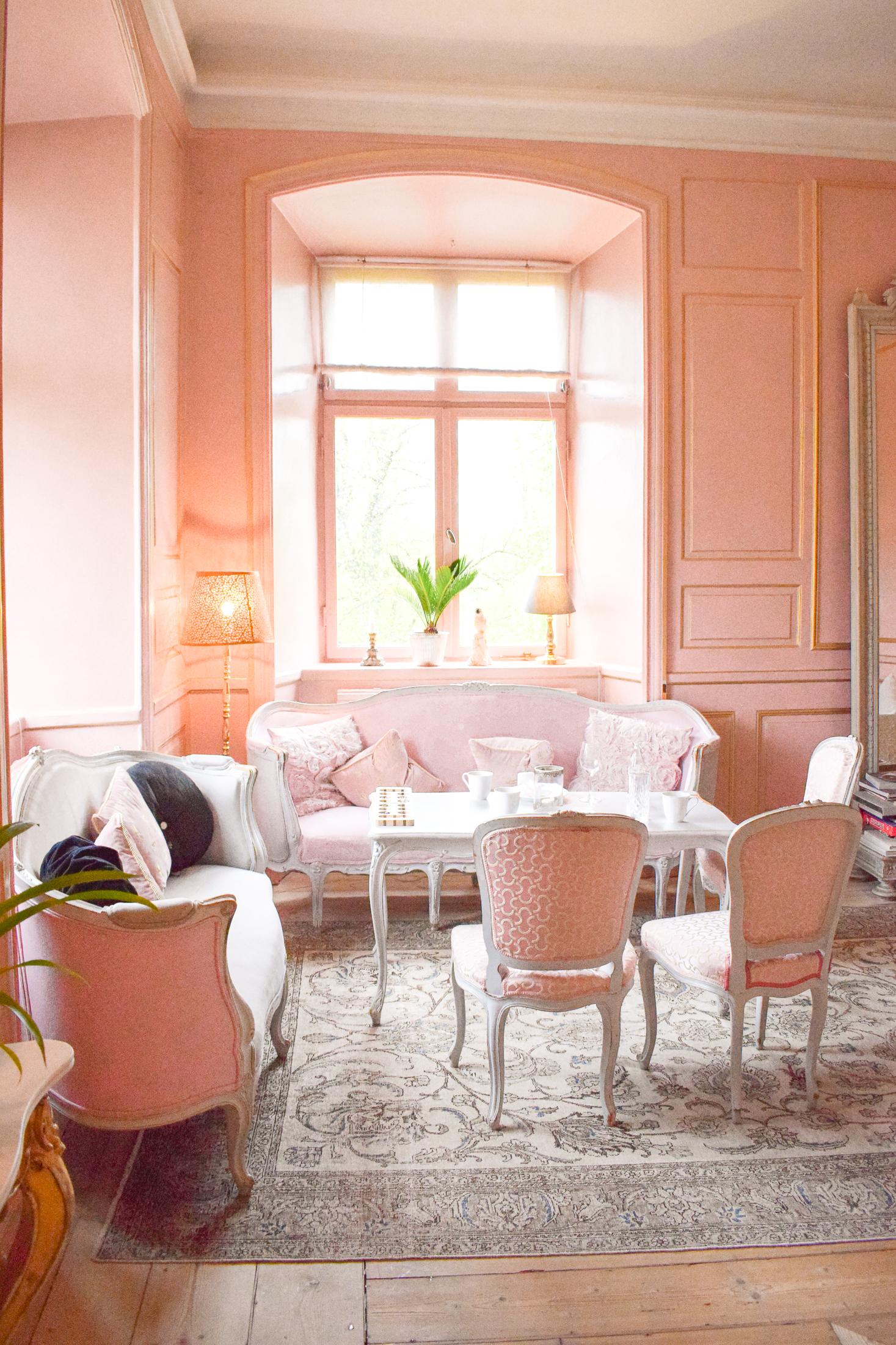 ljusrosa stolar och soffa i rum med ljusrosa väggar.