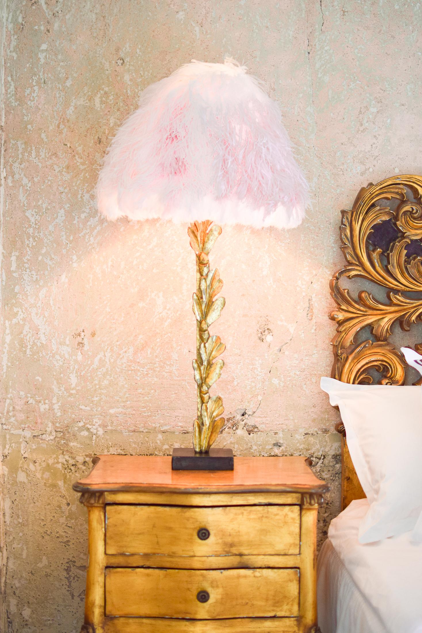 sängbord med en ljusrosa lampskärm på en guldig lampfot.