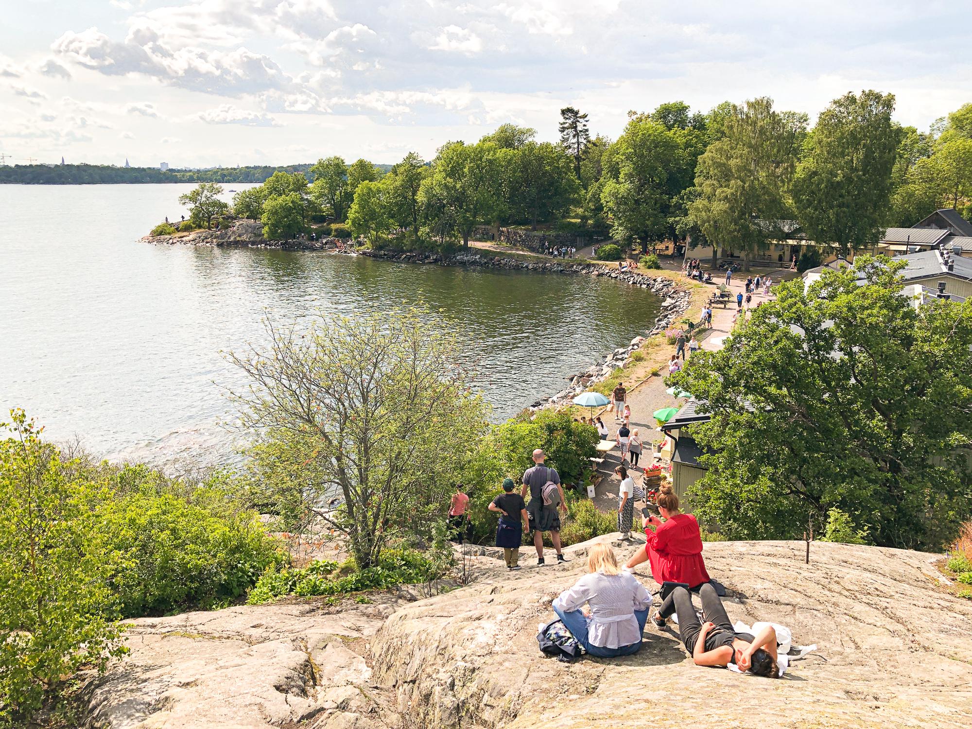folk sitter på klipporna på fjäderholmarna.