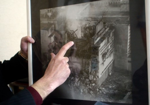 Twenty years after the disaster, Yuri Andreyev, a former senior engineer at the Chernobyl nuclear power plant, pointed to the destroyed Reactor No. 4 in a photo made a few hours after the April 26, 1986, explosion. // Efrem Lukatsky / AP