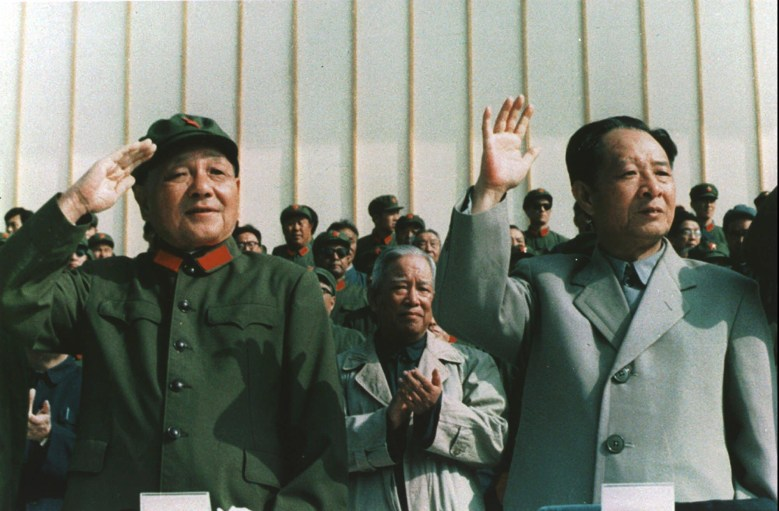 Dressed in People's Liberation Army uniform, Deng Xiaoping, left, chairman of Chinese Military Commission, salutes as he reviews military parade with General-Secretary Hu Yaobang in this file photo taken in September 1981. // Xinhua News Agency via Kyodo