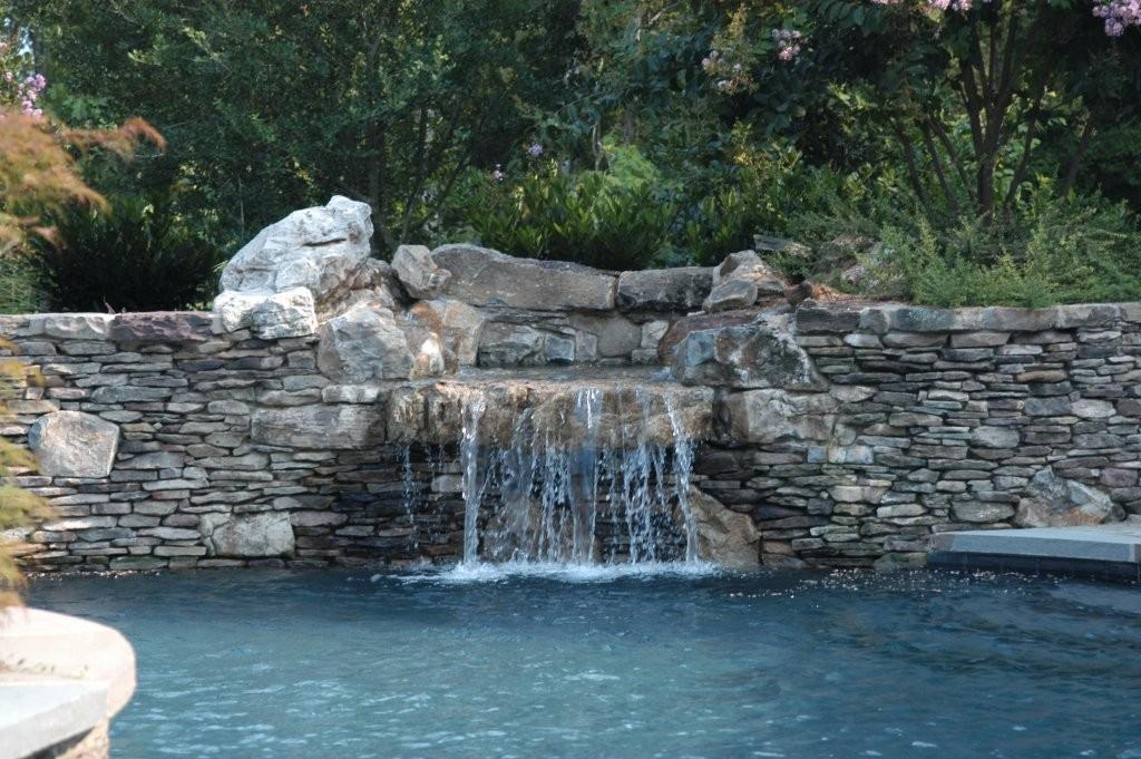 Stone Waterfall Into Swimming Pool From Stone Center Of