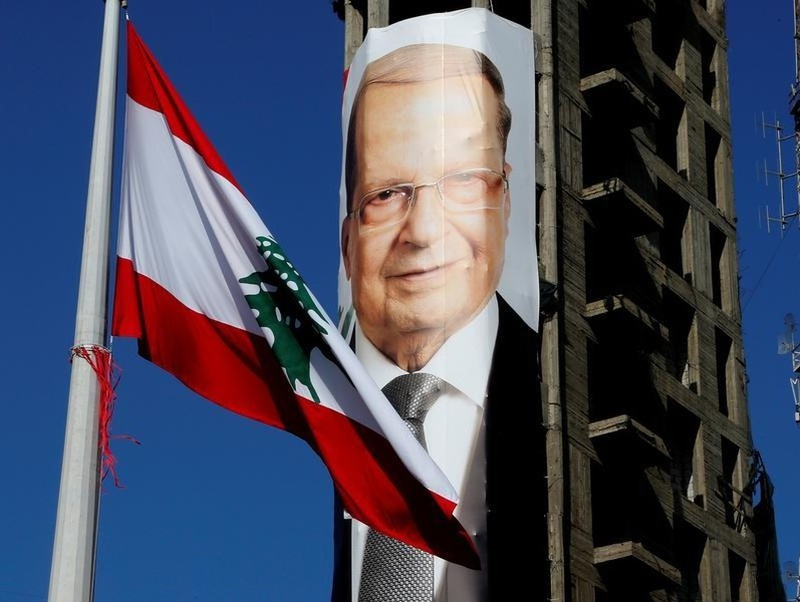 A Lebanese flag flutters near a picture of Christian politician and FPM founder Michel Aoun on a building prior to presidential elections in