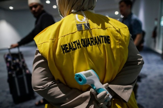 Indonezyjski urzędnik kwarantanny zdrowia posiada skaner termiczny, międzynarodowe lotnisko Soekarno-Hatta, Indonezja
