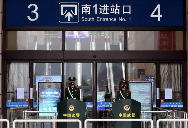 Chińscy oficerowie paramilitarni w maskach stoją na straży przy wejściu do zamkniętego dworca kolejowego Hankou w Wuhan.