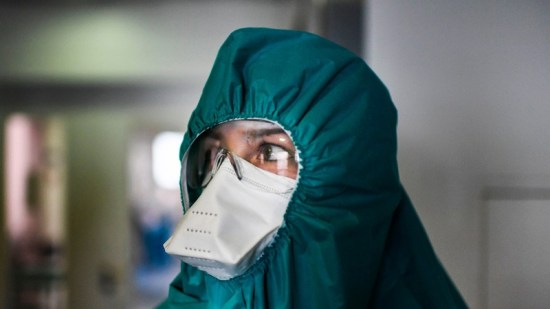 A health worker wearing a protective suit prepares before entering the ICU of COVID-19 in Lisbon.