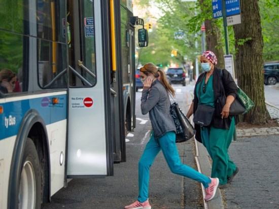 NYC Medical workers wearing masks board an MTA bus amid the coronavirus pandemic.