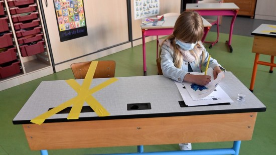 A pupil of the Sainte-Croix elementary school works as half of her writing desk is marked to ensure safe distance, France.