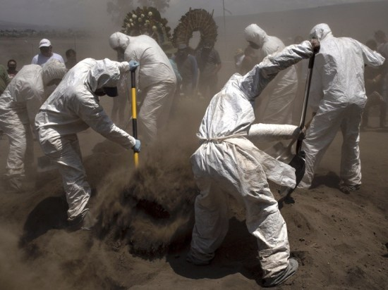 Chalco cemetery workers use protective equipment for COVID-19 to bury the deceased on June 7, 2020 in Mexico City.