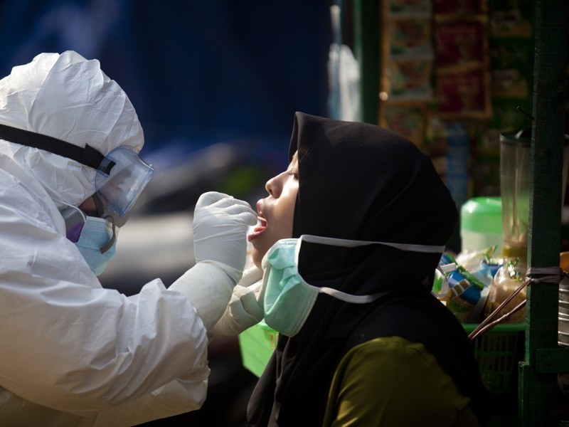 A health worker dressed in a personal protective equipment (PPE) suit is seen getting a swab test from a trader.