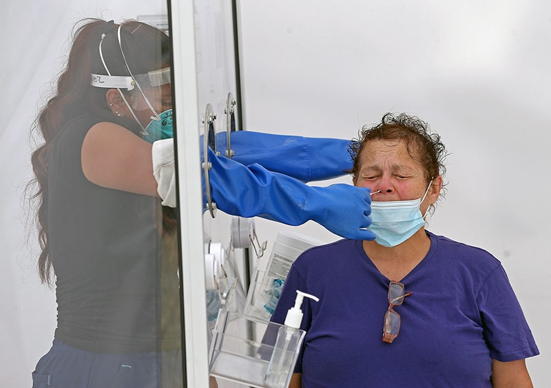 A medical assistant inserts arms through holes in a screen to swab a person's nose at a COVID-19 testing site.