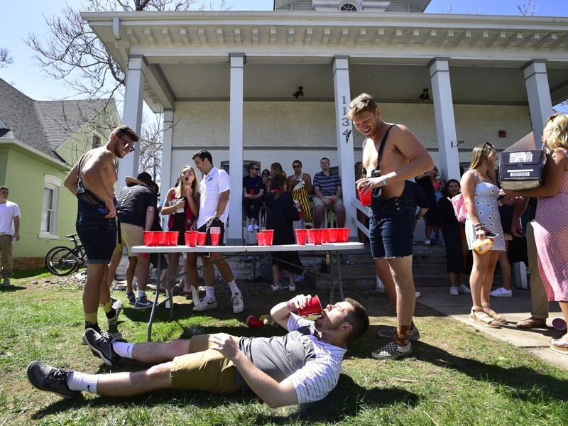 A University of Colorado Boulder student chugs a beer at a graduation party outside of a home, US.