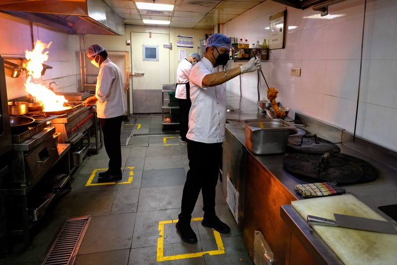 Chefs prepare food as they stand in boxes marked out to assist social distancing