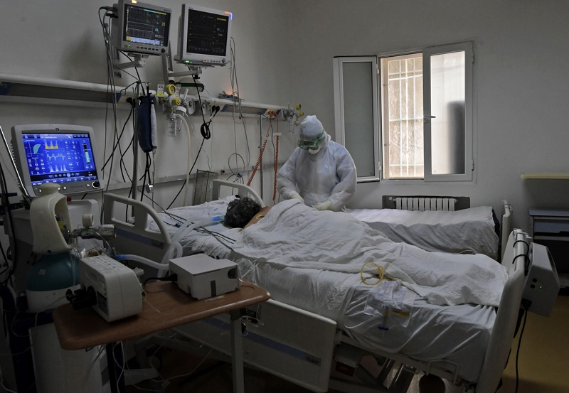 A Tunisian member of the medical staff attends to a coronavirus patient