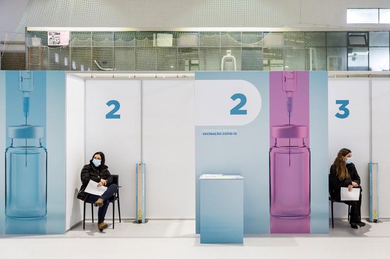 People wait to receive Pfizer-BioNTech's coronavirus vaccines