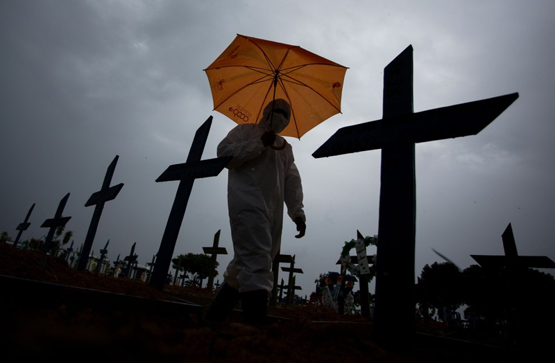 A worker wearing a protective suit and carrying an umbrella walks past the graves of COVID-19 victims, Brazil