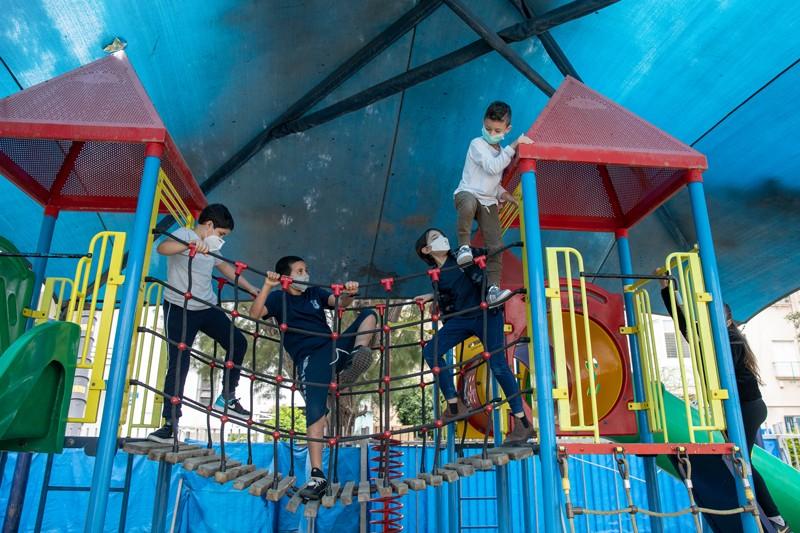 Children wearing masks play in a playground in Tel Nordau school, Israel