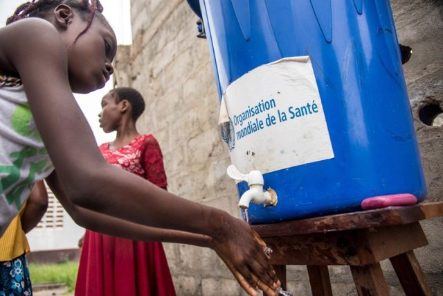 A woman washes her hands from a tank of water bearing a World Health Organization sticker in the Democratic Republic of Congo