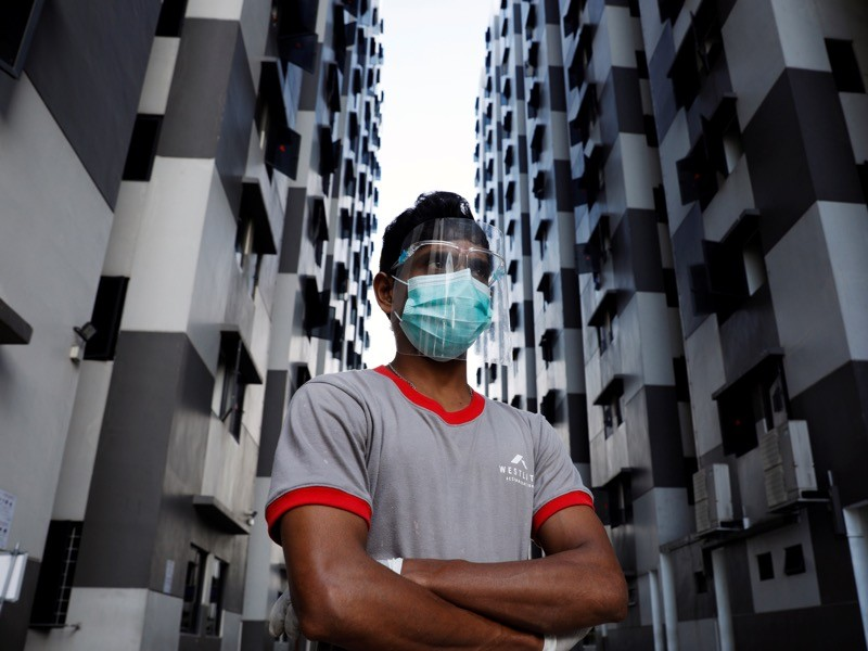 A migrant worker listens as officials give a tour of a dormitory, Singapore.