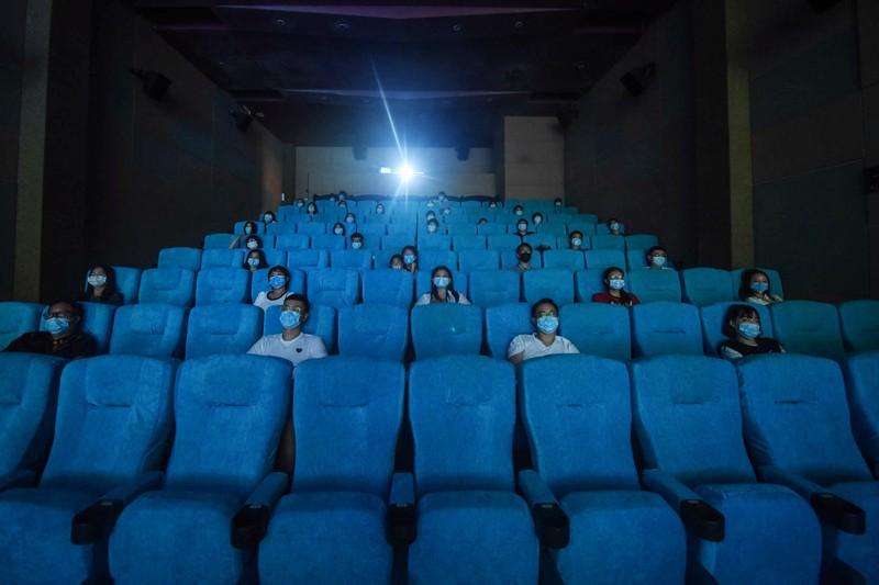 Las personas que usan máscaras se sientan separadas para el distanciamiento social en un cine en Hangzhou, China