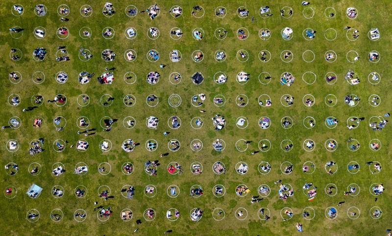 Toma aérea de personas reunidas dentro de círculos pintados en la hierba alentando el distanciamiento social en un parque de San Francisco