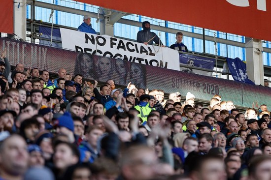 A No Facial Recognition banner with fans in seats at a football match in Cardiff, Wales