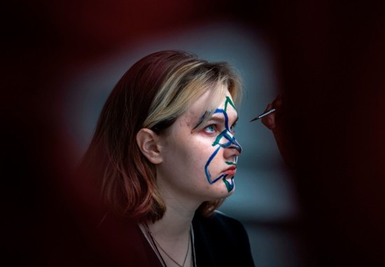 A young woman has blue and green coloured lines painted on her face with a paintbrush held by an unseen person