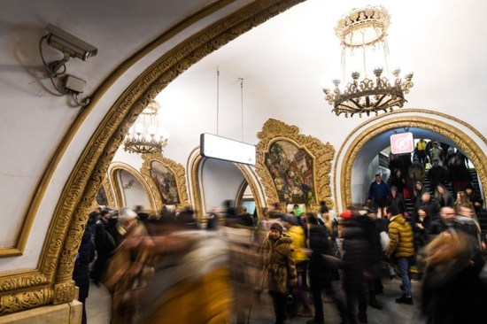 A surveillance camera records crowds passing through an ornately designed metro station in Moscow