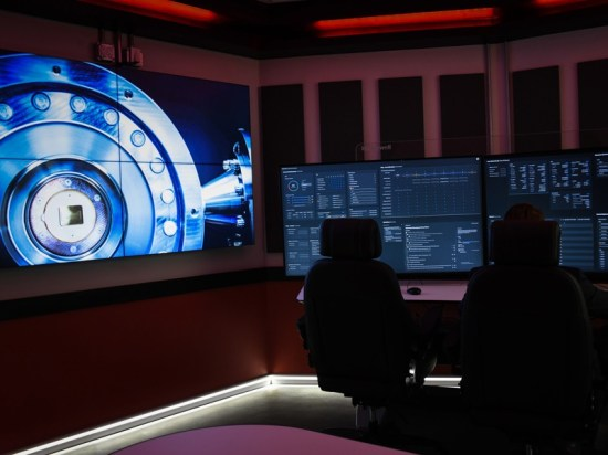 Two desk chairs in front of large screens in a dimly lit room with a picture of the vacuum chamber on the wall.