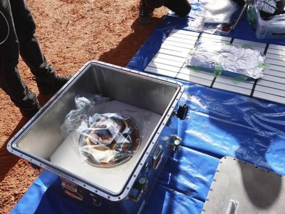 JAXA members pick up a capsule dropped by Hayabusa2 in Woomera, South Australia.