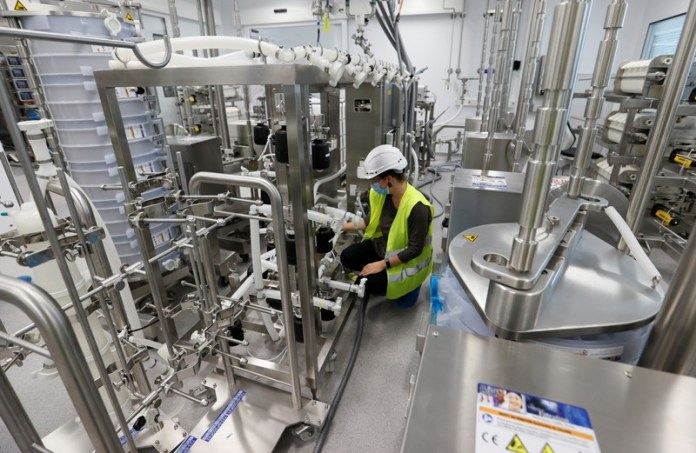 Worker in a hard hat and hi-vis vest setting up a vaccine production line in a factory in Switzerland