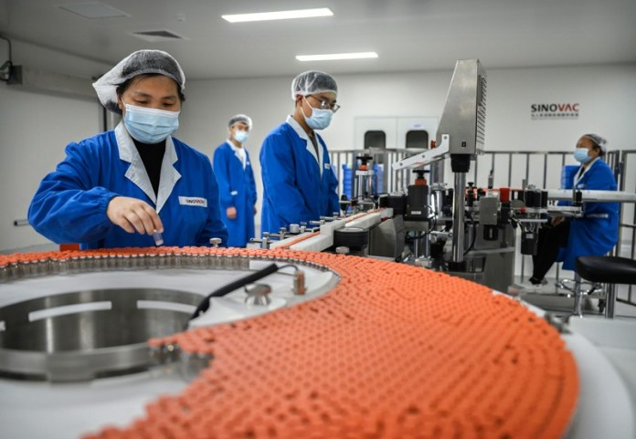 Workers in blue overalls, face masks and hairnets work on a production line checking vials of a vaccine in China