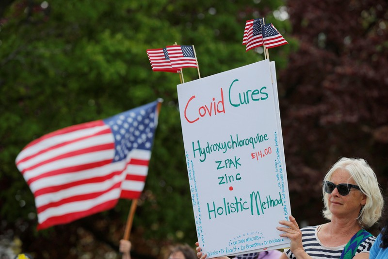 """A woman holds a sign listing """"Covid Cures,"""" including hydroxychloroquine at a protest event in the US"""