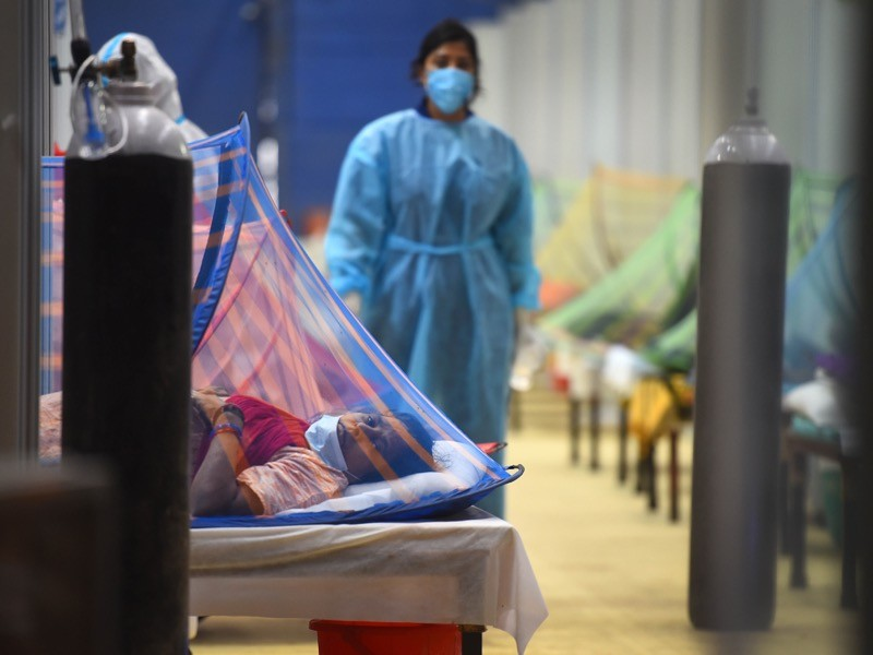A masked healthcare worker walks between hospital beds.