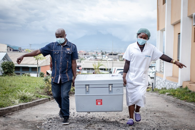 Two health workers carry a large crate containing COIVD-19 vaccines up a hill in Goma, Democratic Republic of Congo