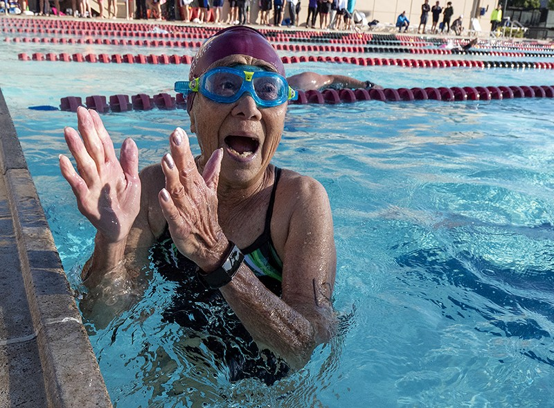 An older woman in a swimming pool, clapping to celebrate her victory in a race.