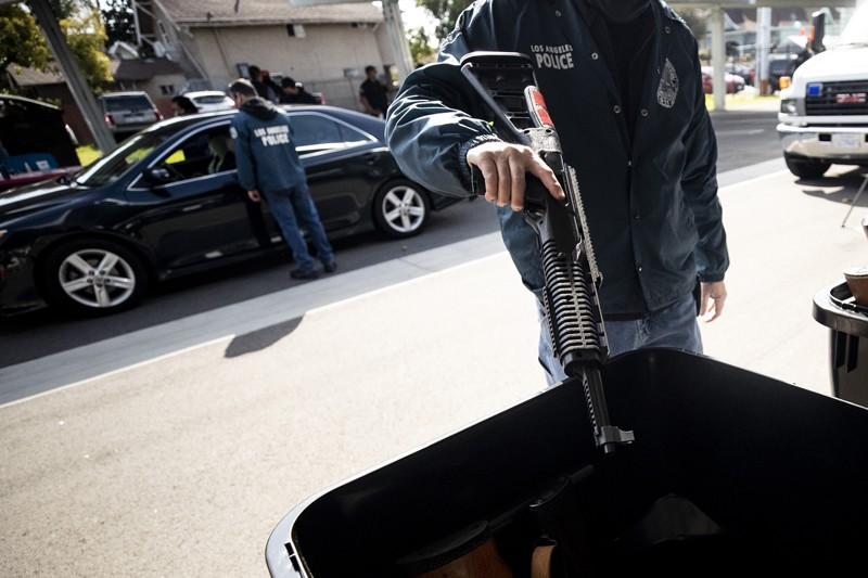 A Los Angeles police officer throws assault rifle into a garbage container on the street during an anonymous gun buyback event