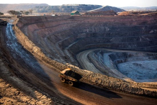 A truck drives around the edge of a open pit copper mine at sunset