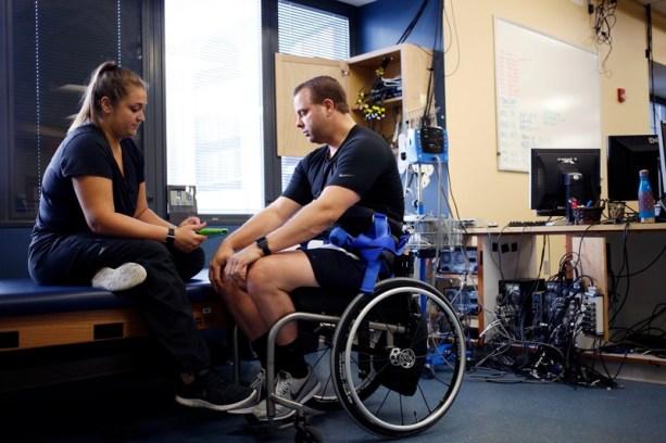 Katie Pfost (Esquerda) controla o estimulador da coluna vertebral de Rob Summers com um tablet antes de conduzir o treinamento da locomotiva na esteira