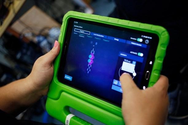 Katie Pfost controla o estimulador espinhal de Rob Summers com um tablet