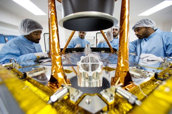 Engineers discussing further steps to disassemble the spacecraft's sun shield baffle for further inspections.