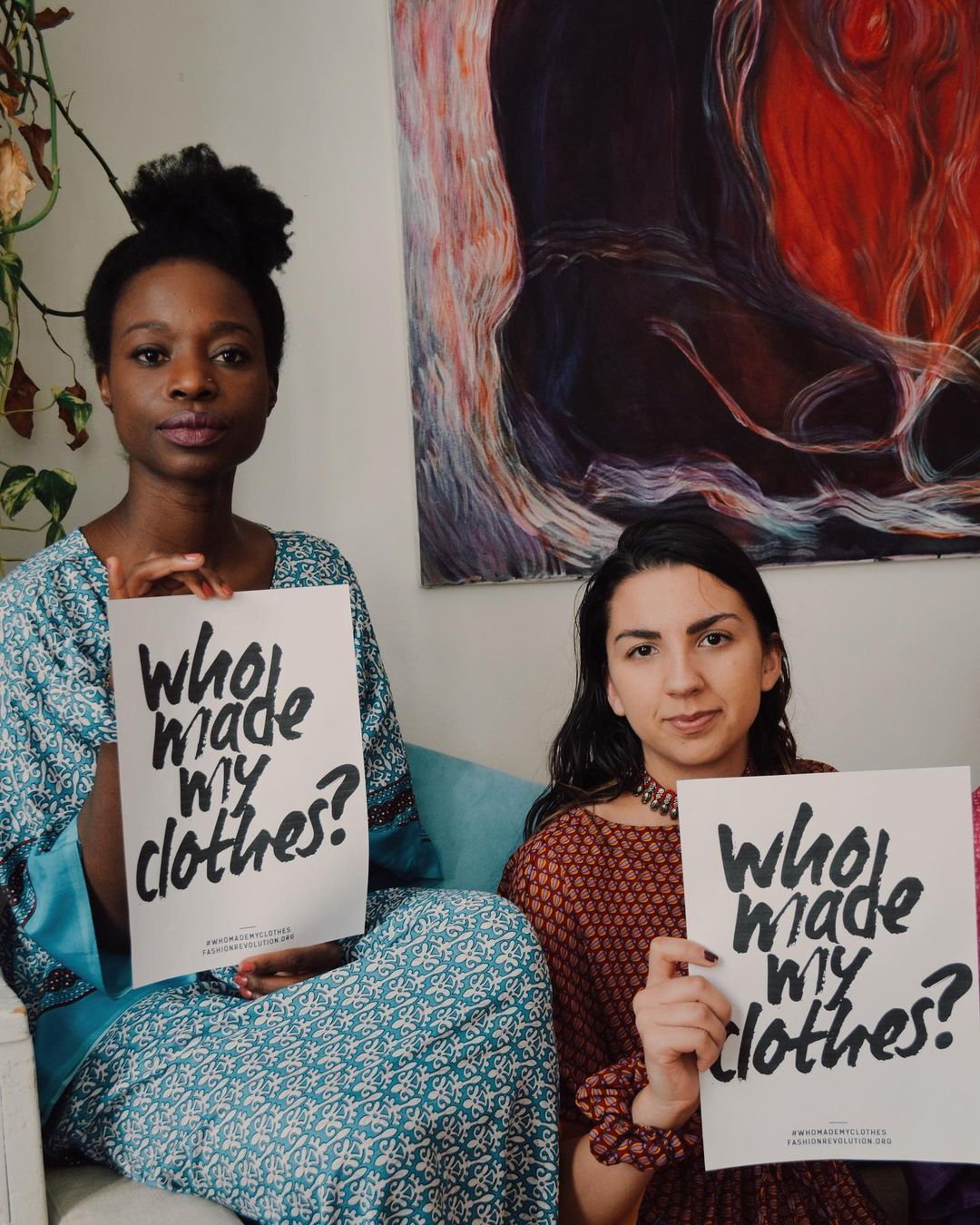 two women holding who made my clothes sign