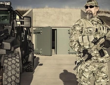 Um guarda armado fica parado na entrada do Projeto Condomínio Sobrevivência