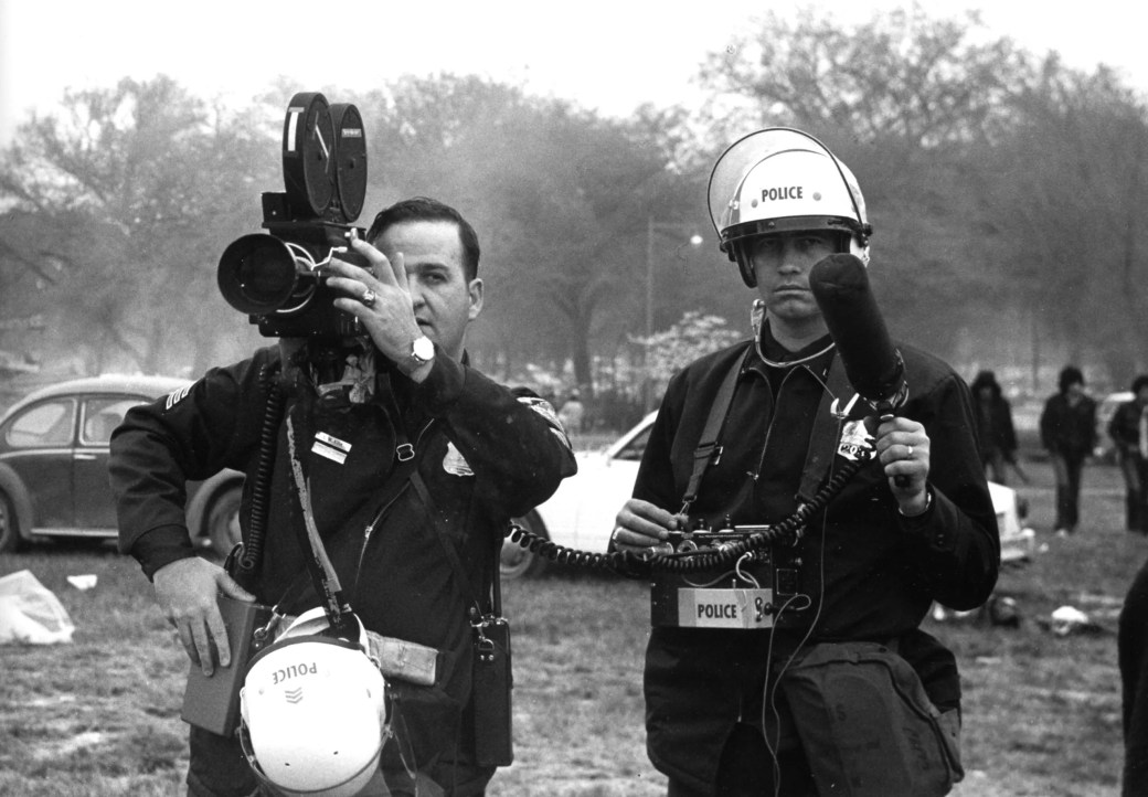 Two members of the NYPD surveillance team holding video and audio recording equipment