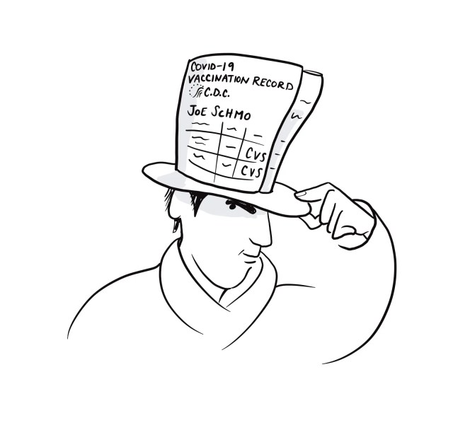 Person wearing a hat covered in an enlarged copy of their vaccination card.