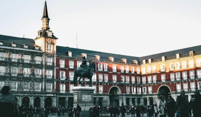 Travelers exploring a historic plaza in Madrid, Spain
